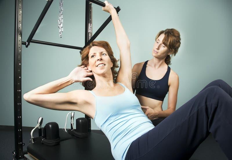 Pilates mit einem Kursleiter stockfotos