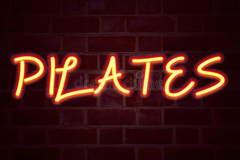 Pilates neon sign on brick wall background. Fluorescent Neon tube Sign on brickwork Business concept for Fitness Balance Workout E. Xercise 3D rendered Front stock photography