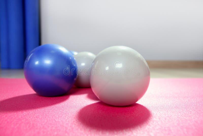 Pilates que tonifica esferas sobre a esteira vermelha da ioga imagem de stock
