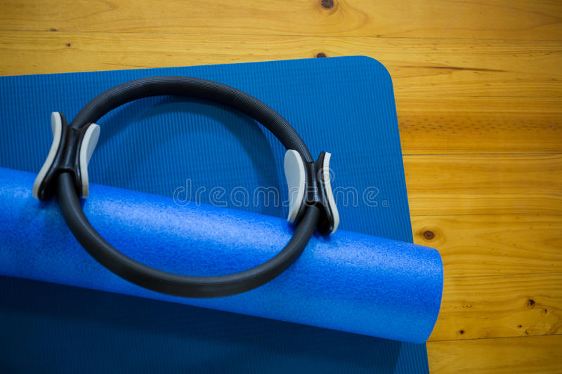 Pilates ring and exercise mat kept on wooden floor stock images