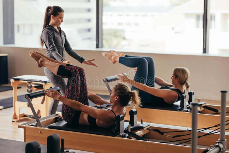 Pilates-Trainer, der Frauen an der Turnhalle anweist lizenzfreie stockfotos