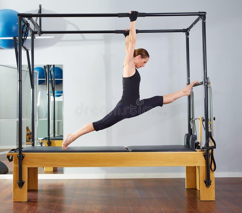 Pilates woman in cadillac legs split reformer stock image