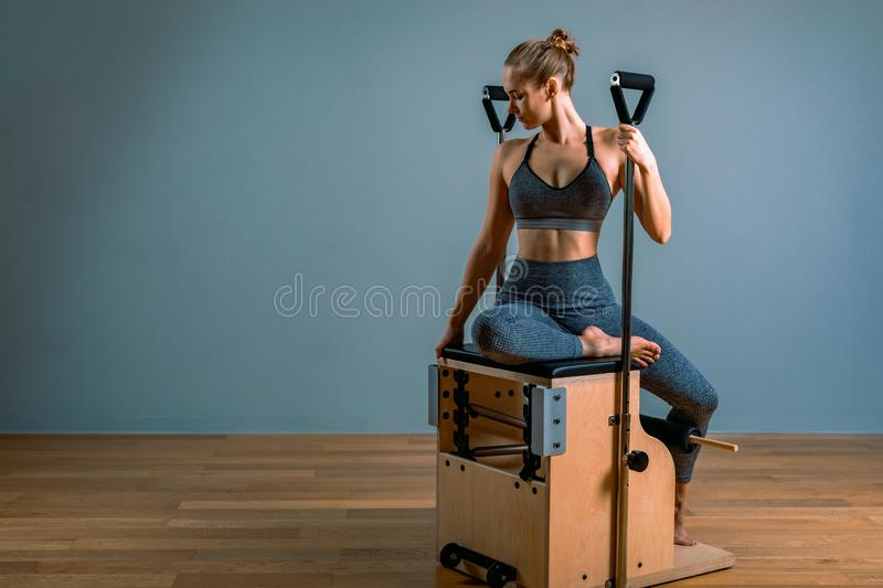 Pilates woman in a Cadillac reformer doing stretching exercises in the gym. Fitness concept, special fitness equipment stock photos