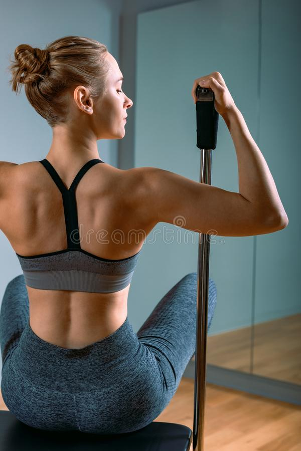 Pilates woman in a Cadillac reformer doing stretching exercises in the gym. Fitness concept, special fitness equipment stock images