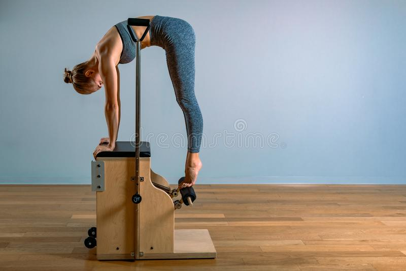 Pilates woman in a Cadillac reformer doing stretching exercises in the gym. Fitness concept, special fitness equipment royalty free stock photo