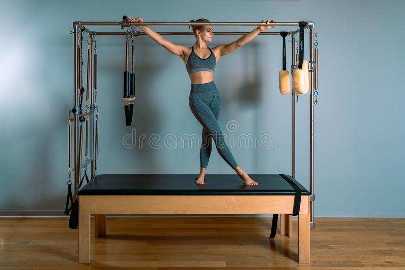 Pilates woman in a Cadillac reformer doing stretching exercises in the gym. Fitness concept, special fitness equipment. Healthy lifestyle, plastic. Copy space royalty free stock images
