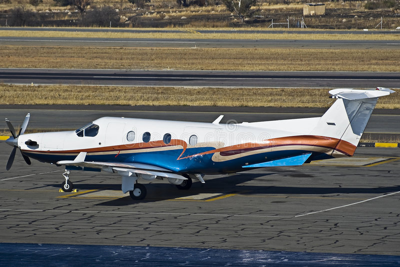 Pilatus PC-12/45. A 1999 model, Pilatus PC-12/45 parked on the the apron. Seen here sporting it's new (2007) paint job. In the foreground is a smidgen of royalty free stock image