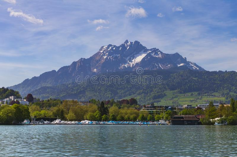 Pilatus snow mountain and boats port in lake Lucern, Switzerland royalty free stock image