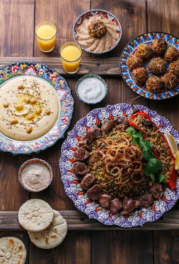 Pilau do Oriente Médio ou árabe com hummus, falafel, mergulho da beringela e opinião superior dos pães árabes imagem de stock royalty free