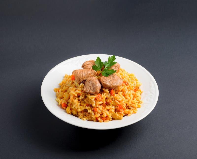 Pilau perfumado Pilau, arroz fritado com carne e vegetais em uma placa branca Isolado no cinza foto de stock