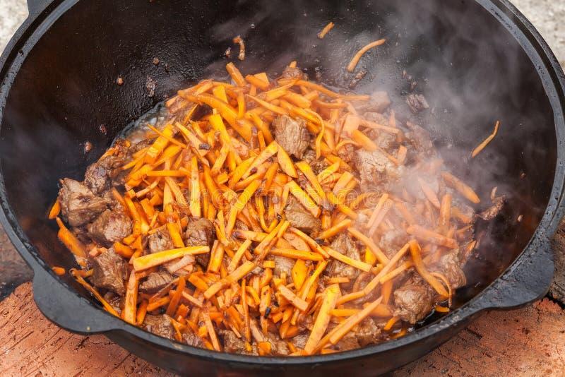 Pilau, pilaw, plov, arroz com carne na bandeja Processo de cozimento fotografia de stock