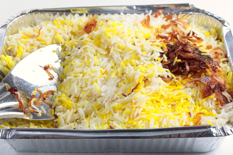 Pilau rice takeaway. An indian restaurant's Pilau rice with onion garnish takeaway in an aluminium tray with a rice serving spoon stock photos