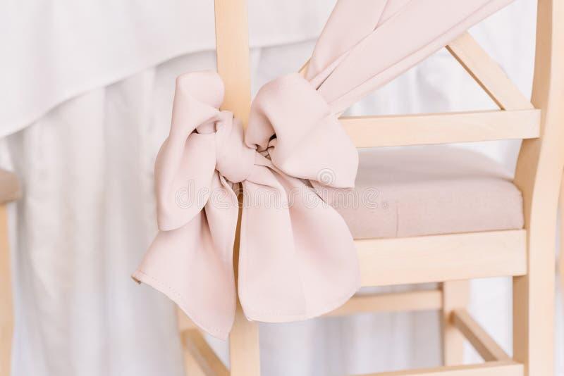 Pilbåge av försiktig rosa färg på en stol tillbaka royaltyfria bilder
