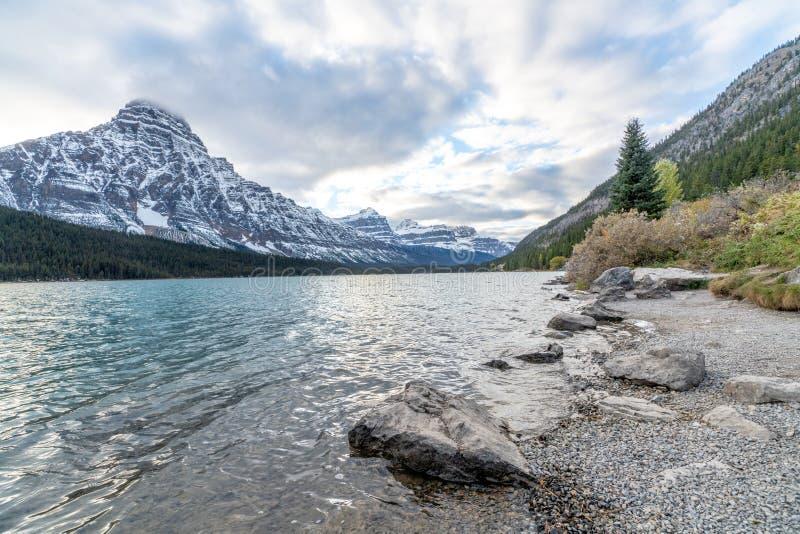 Pilbågeflod i den Banff nationalparken med områden för snölockberg under molnig blå himmel, fotografering för bildbyråer