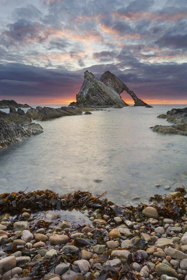Pilbågen-fidle vaggar soluppgånglandskap på kusten av Skottland på molnig morgon royaltyfria bilder