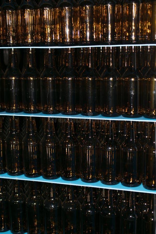Pile énorme de bouteilles en verre vides sur la table bleue photo libre de droits