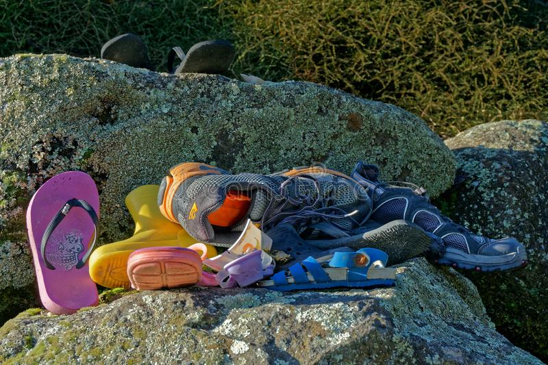 A pile of abandoned or lost shoes and assorted footwear. Left at the beach or washed up stock photo
