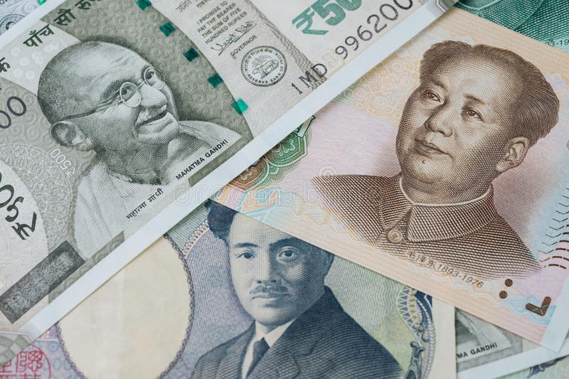 Pile of asian leading countries new emerging market money banknotes, indian rupee, chinese yuan and japanese yen, searching for y stock image