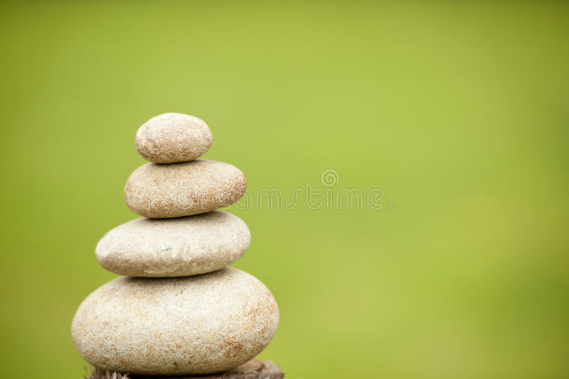 Pile of balanced rocks against green background royalty free stock photo