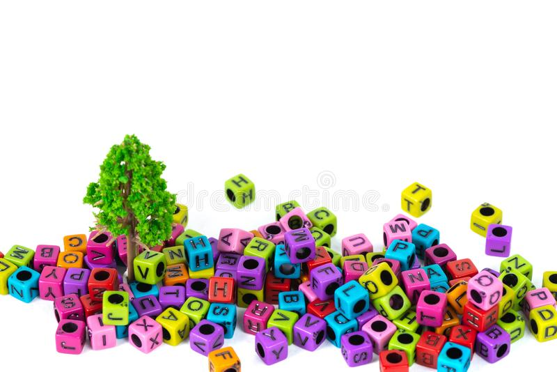 Pile of letter bead or beads with alphabet and little tree on white background. Pile of beads or letter bead with alphabet and little tree on white background royalty free stock photos