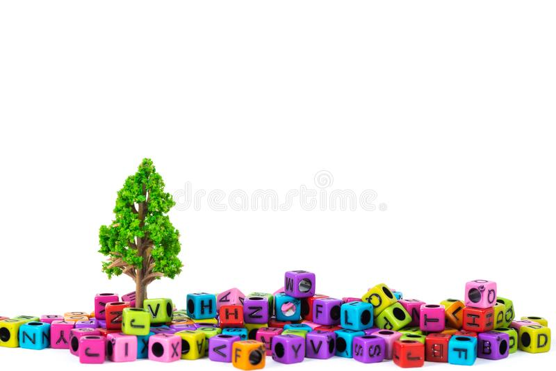 Pile of letter bead or beads with alphabet and little tree on white background. Pile of beads or letter bead with alphabet and little tree on white background royalty free stock photo