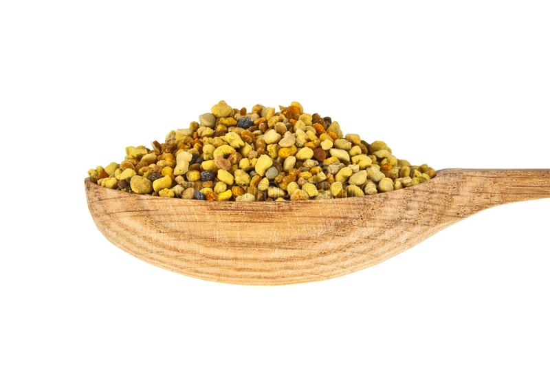 Pile of bee pollen in wooden spoon on a white backround stock photo
