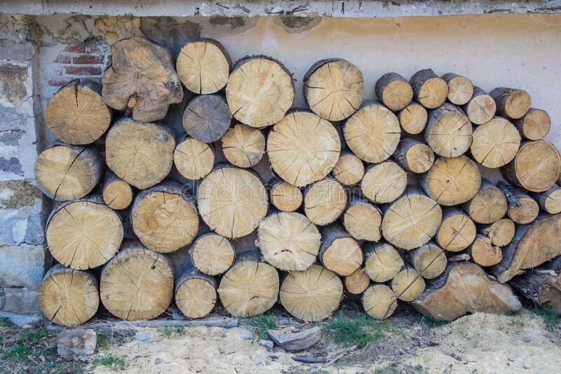 Pile of big round woods in front of a house. Logs, Fuel for heating. Wooden firewood stacked. Natural wood background. Fuel for heating during the winter stock photo