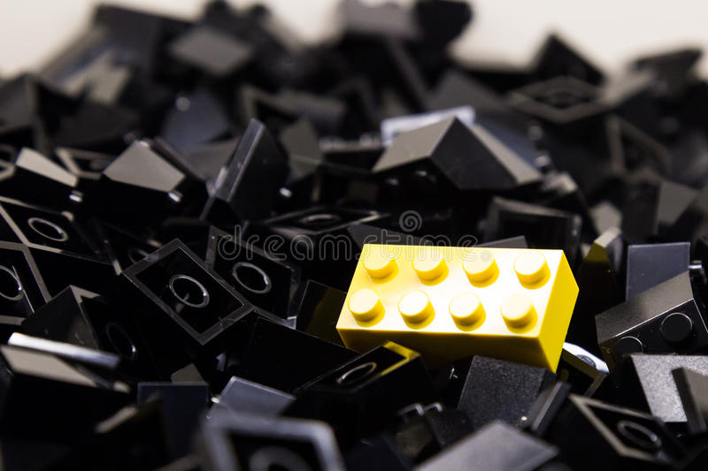 Pile of black color building blocks with selective focus and highlight on one particular yellow block using available light.  stock photography