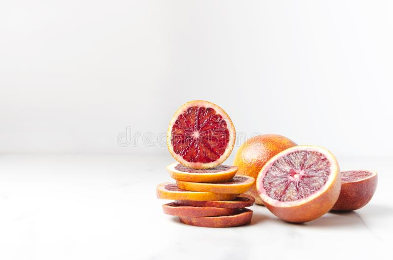 Pile of blood orange slices and halfs of it on the white table.Empty space for your design stock photo