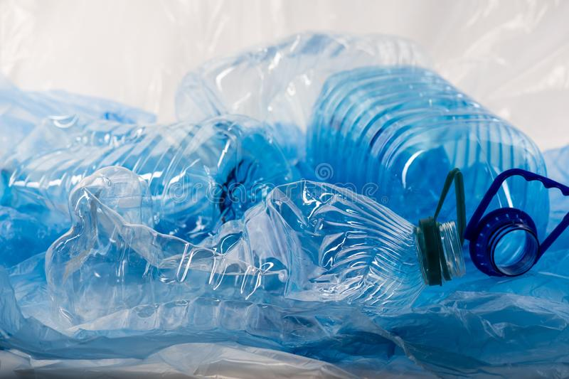 Pile of blue clear plastic bottles and bags being thrown together royalty free stock image