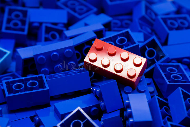 Pile of blue color building blocks with selective focus and highlight on one particular red block using available light.  stock photos