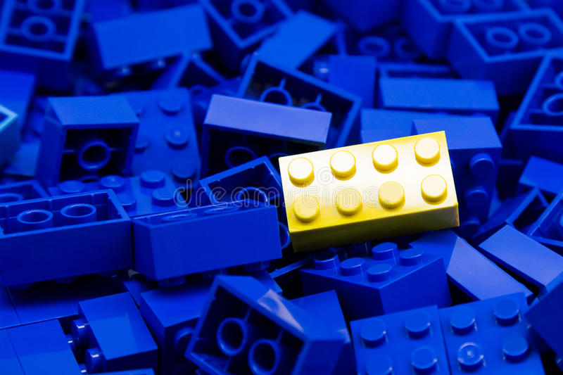 Pile of blue color building blocks with selective focus and highlight on one particular yellow block using available light.  stock photography