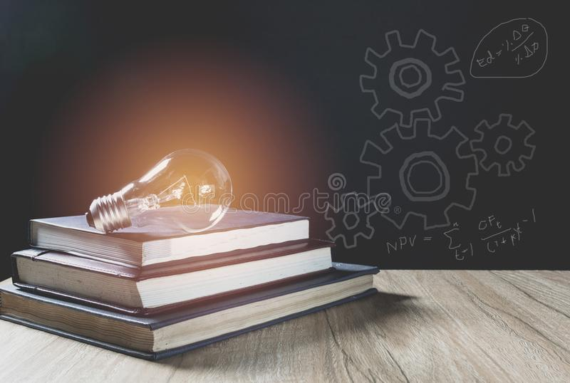Pile of book with glowing light bulb over it on wood wall. Pile of book with glowing light bulb over it. Knowledge, education concept royalty free stock photo