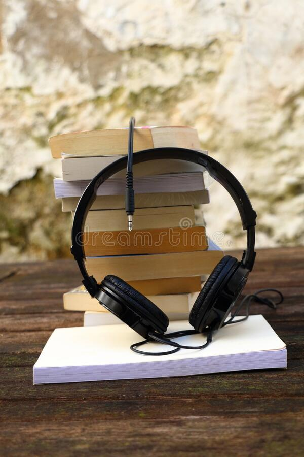 A pile of books audio headset on a wooden table. Different books, novels, poems, short stories, thrillers and romance. Audio book and audio headset stock photography