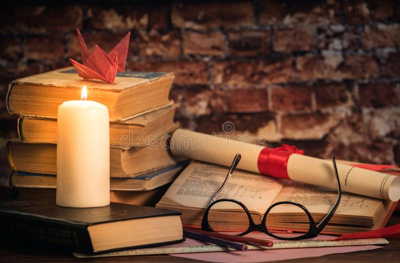 A pile of books, book, glasses, candle, origami, scroll on the wood desk stock images