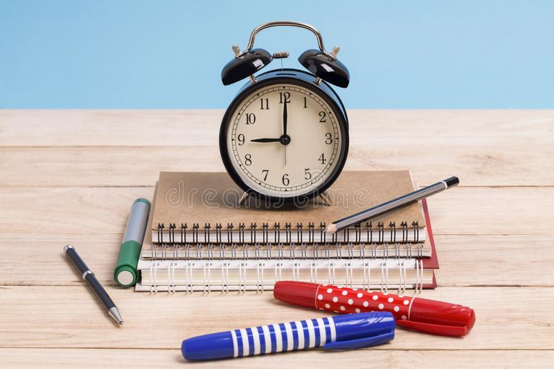 A pile of books and with coloured pen and alarm clock on a wooden with blue background royalty free stock photography