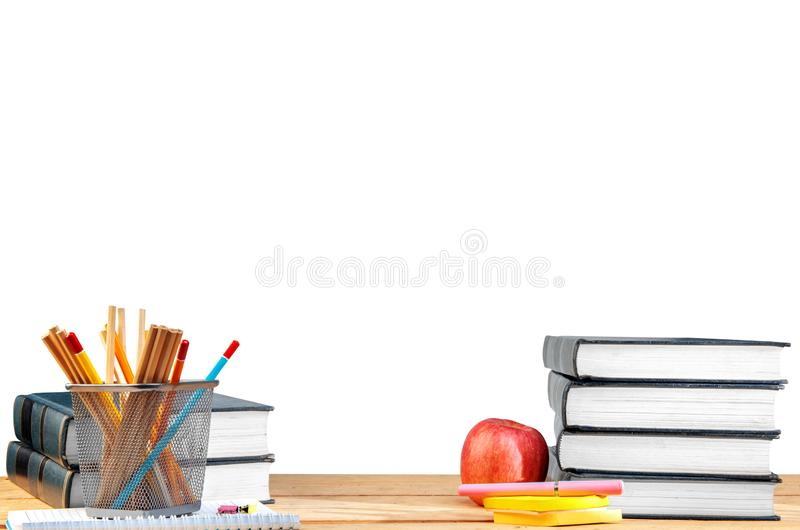 Pile of books with notes paper and pen, apple and pencils in basket container on wooden table stock image