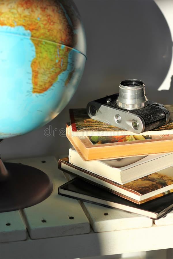 Pile of books, old film photo camera and a globe on white wooden table. Concept of travel, planning a dream trip royalty free stock photography