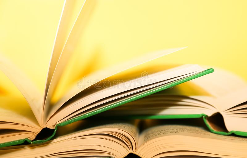 Yellow book stack, book pages turning, over a yellow background. stock images