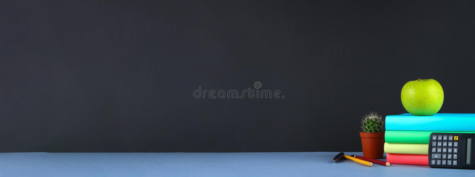 A pile of books and stationery on a chalkboard background. Work desk, education, school. Banner. stock photos