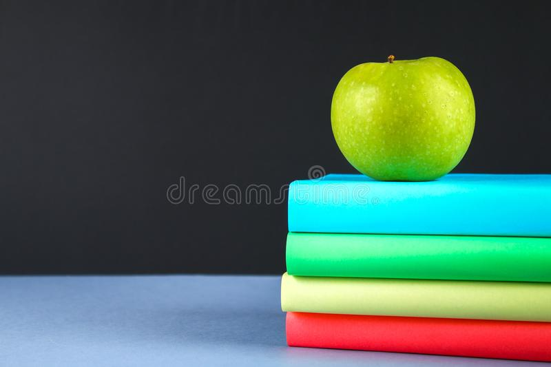 A pile of books and stationery on a chalkboard background. Work desk, education, school. stock photos