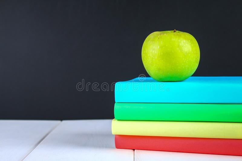 A pile of books and stationery on a chalkboard background. Work desk, education, school. royalty free stock photos