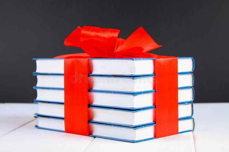 A pile of books tied with a red ribbon on a white wooden table. A gift on the background of a chalkboard. stock photo
