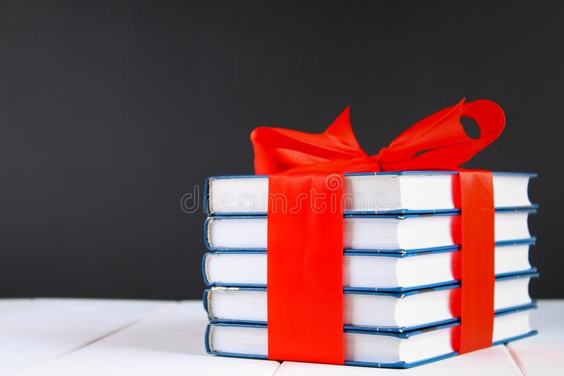 A pile of books tied with a red ribbon on a white wooden table. A gift on the background of a chalkboard. royalty free stock images