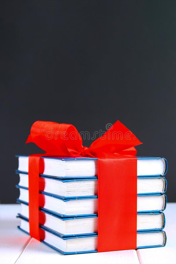 A pile of books tied with a red ribbon on a white wooden table royalty free stock images