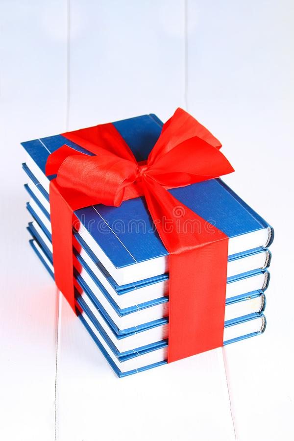 A pile of books tied with a red ribbon on a white wooden table. A gift on the background of a chalkboard stock photo