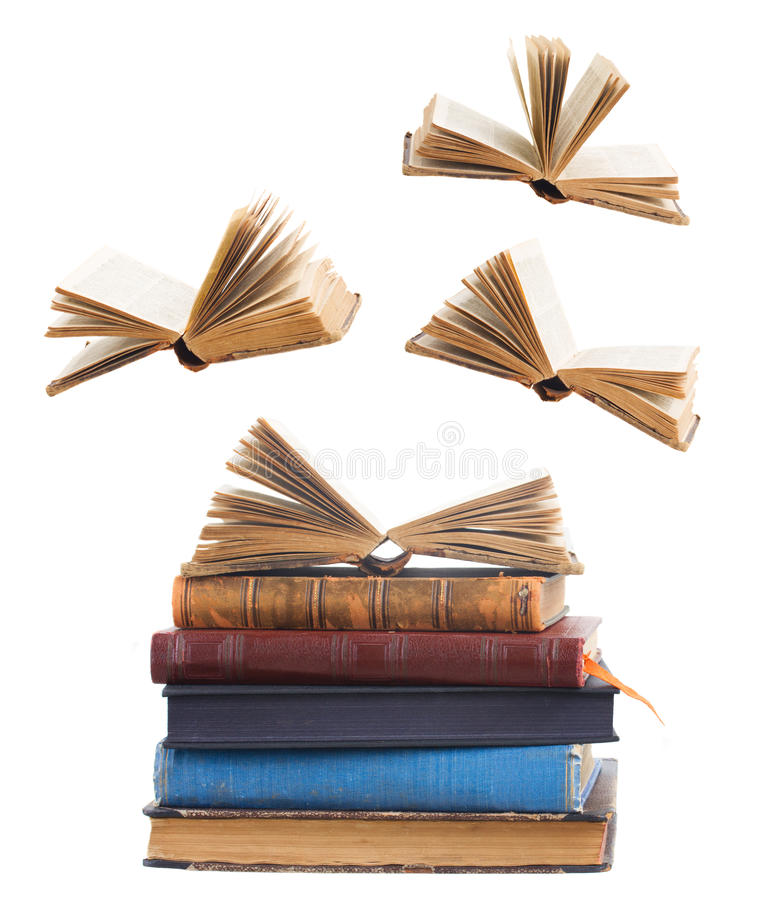 Pile of books. Tower of old books and flying open books isolated on white background stock photography