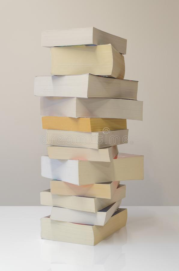 Pile of books on the white table and light grey background. Vertical picture of pile of books on the white table with light grey background stock images