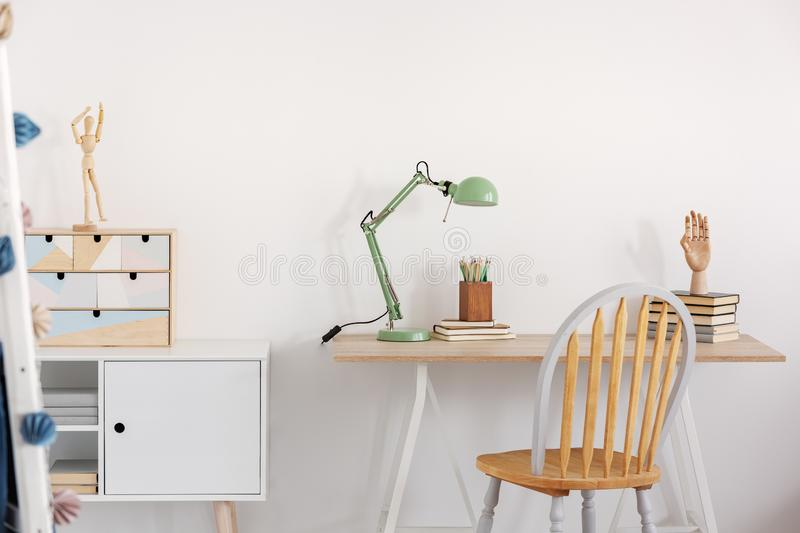 Pile of books, wooden hand and industrial mint colored lamp on stylish wooden desk in white kid`s bedroom. Pile of books, hand and industrial mint colored lamp royalty free stock images