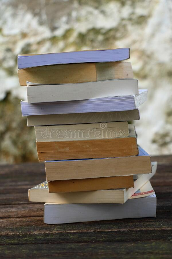 A pile of books on a wooden table. Different books, novels, poems, short stories, thrillers and romance stock photos